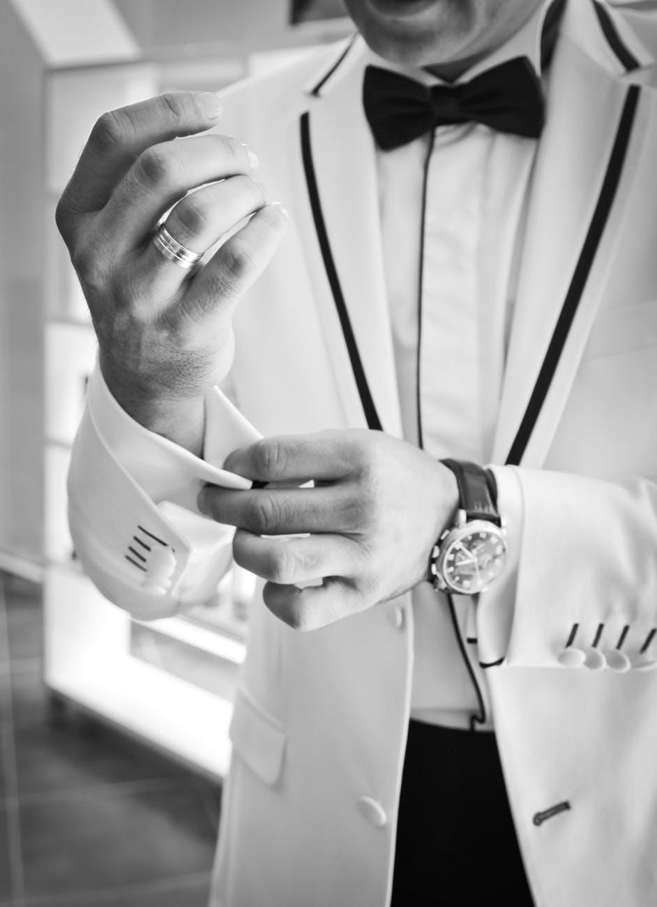 man wearing tuxedo in grayscale photography
