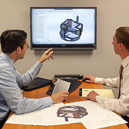 Two engineers sitting at a table to review designs on screen