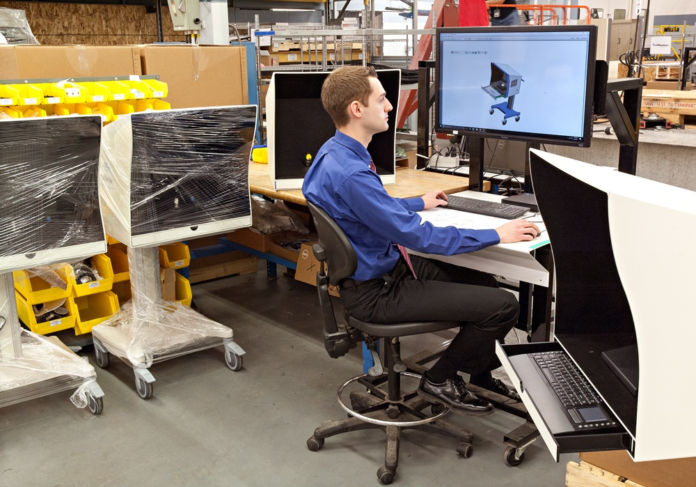 Engineer reviewing drawings on manufacturing floor with 3 machines on wheels