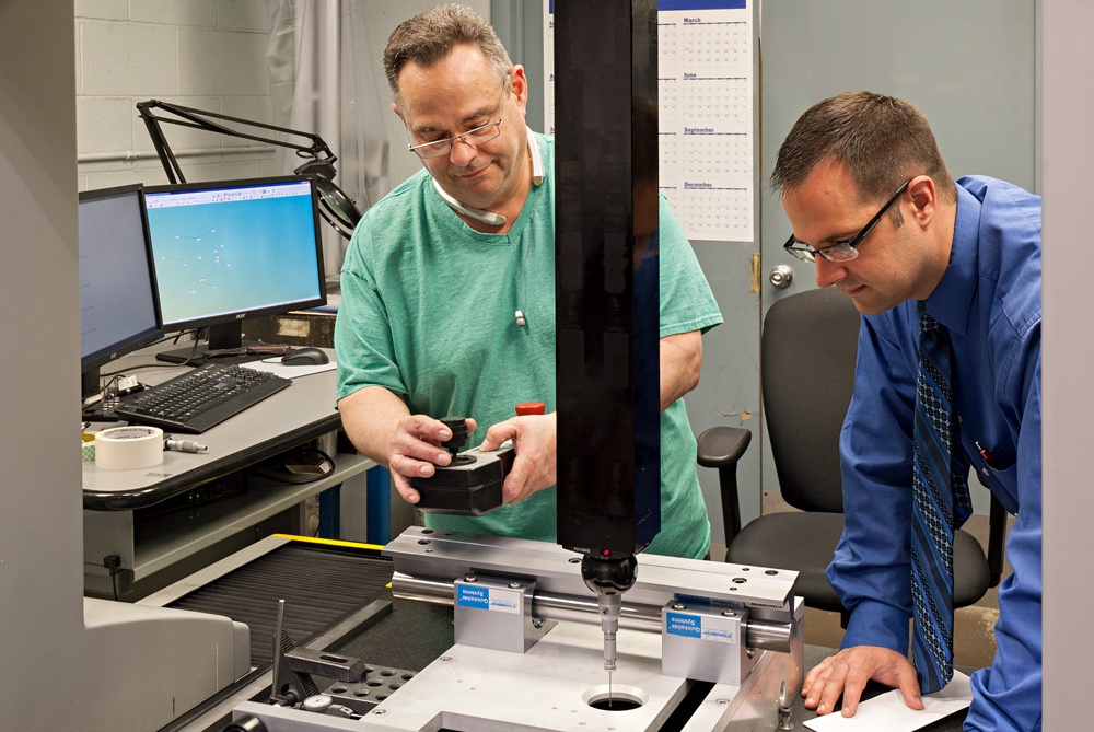 Quality and mechanical engineers inspecting a metal part on a CMM machine