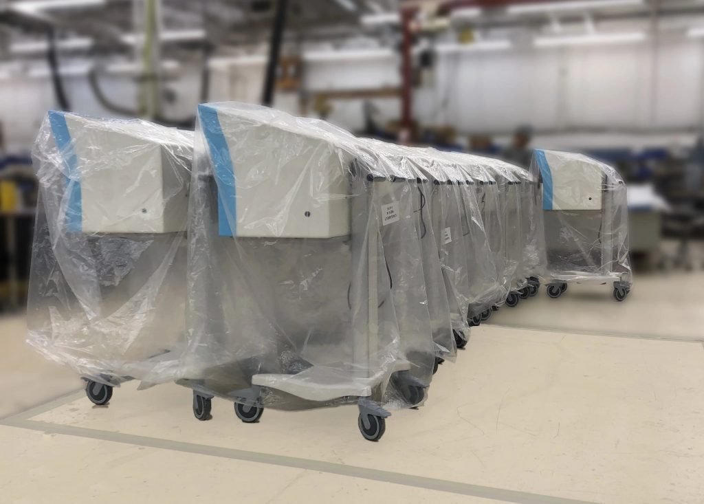 Medical Devices on wheels covered in plastic, ready for shipment.