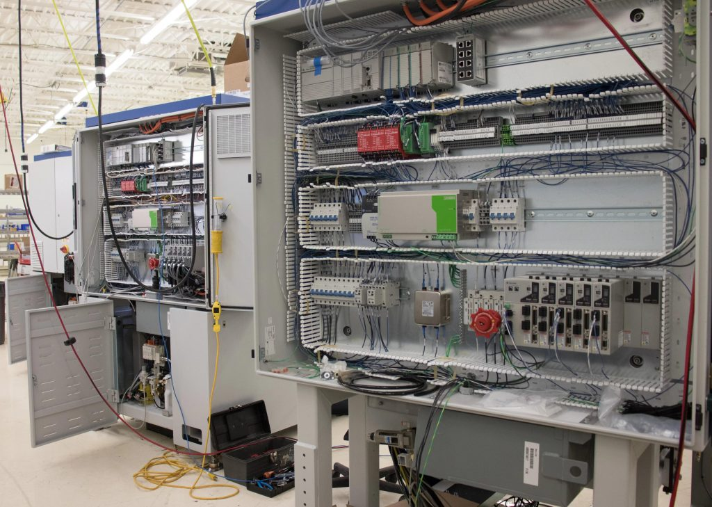 Three machines in production showing electrical assembly in the back of machines