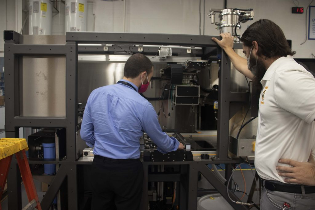 Engineers analyzing a machine's prototype build on the manufacturing floor to review DFMA