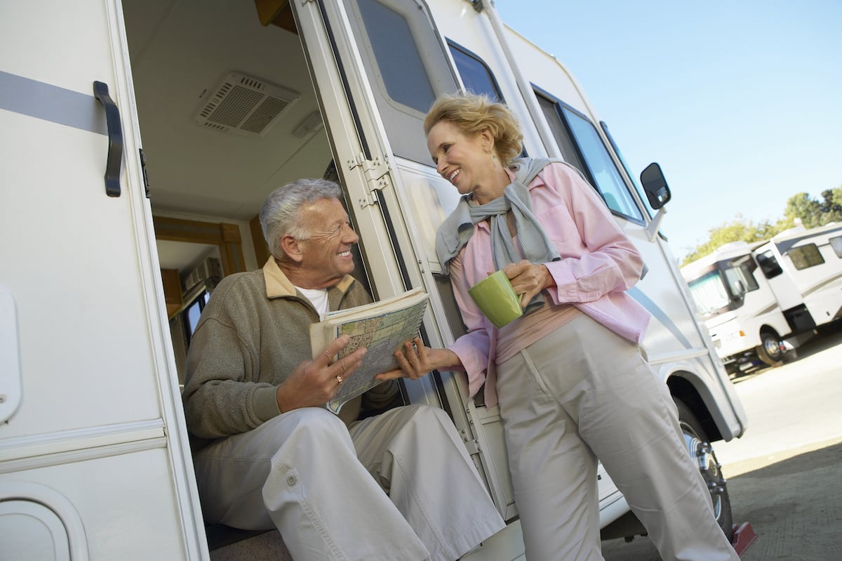 Senior Couple Hold a Map and Plan Their Journey by Their Motor Home