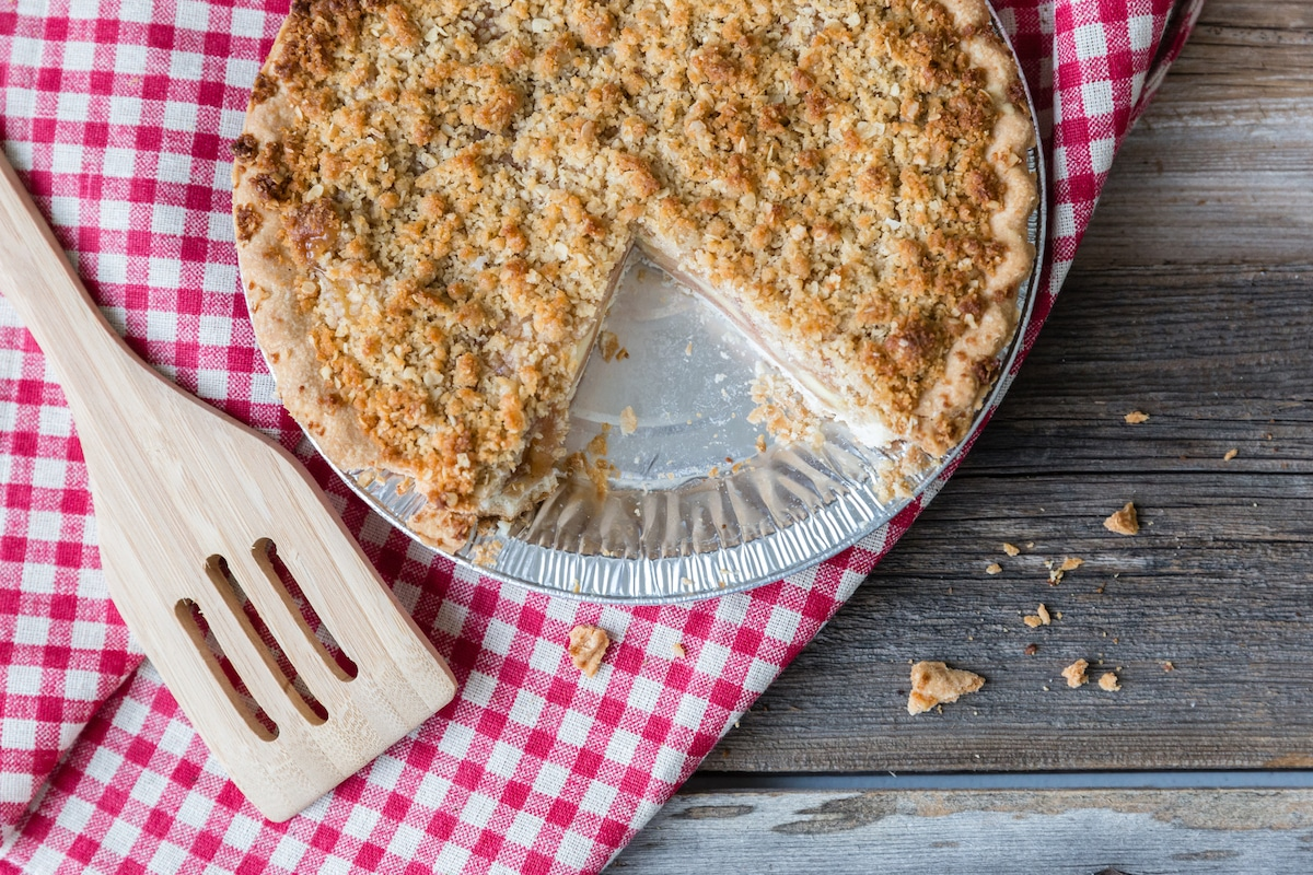 horizontal image of a whole apple crumble pie with portion removed sitting on a red checkered cloth.