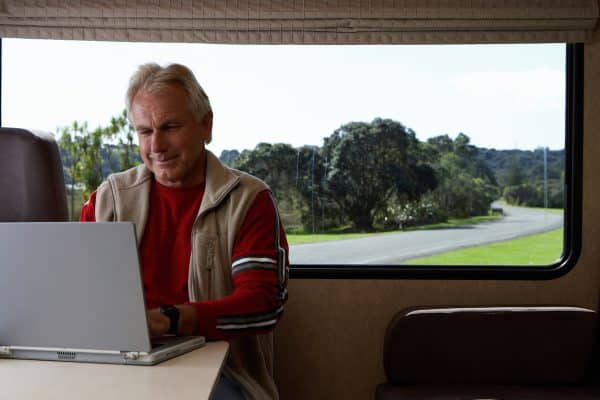 Mature man using laptop inside motor home