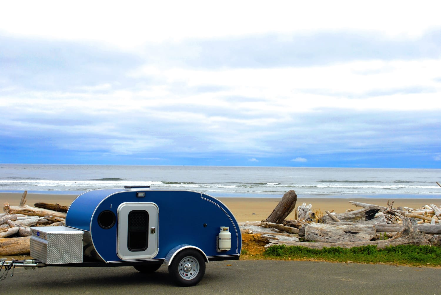 A blue teardrop camping trailer on the roadside along the Oregon Coast