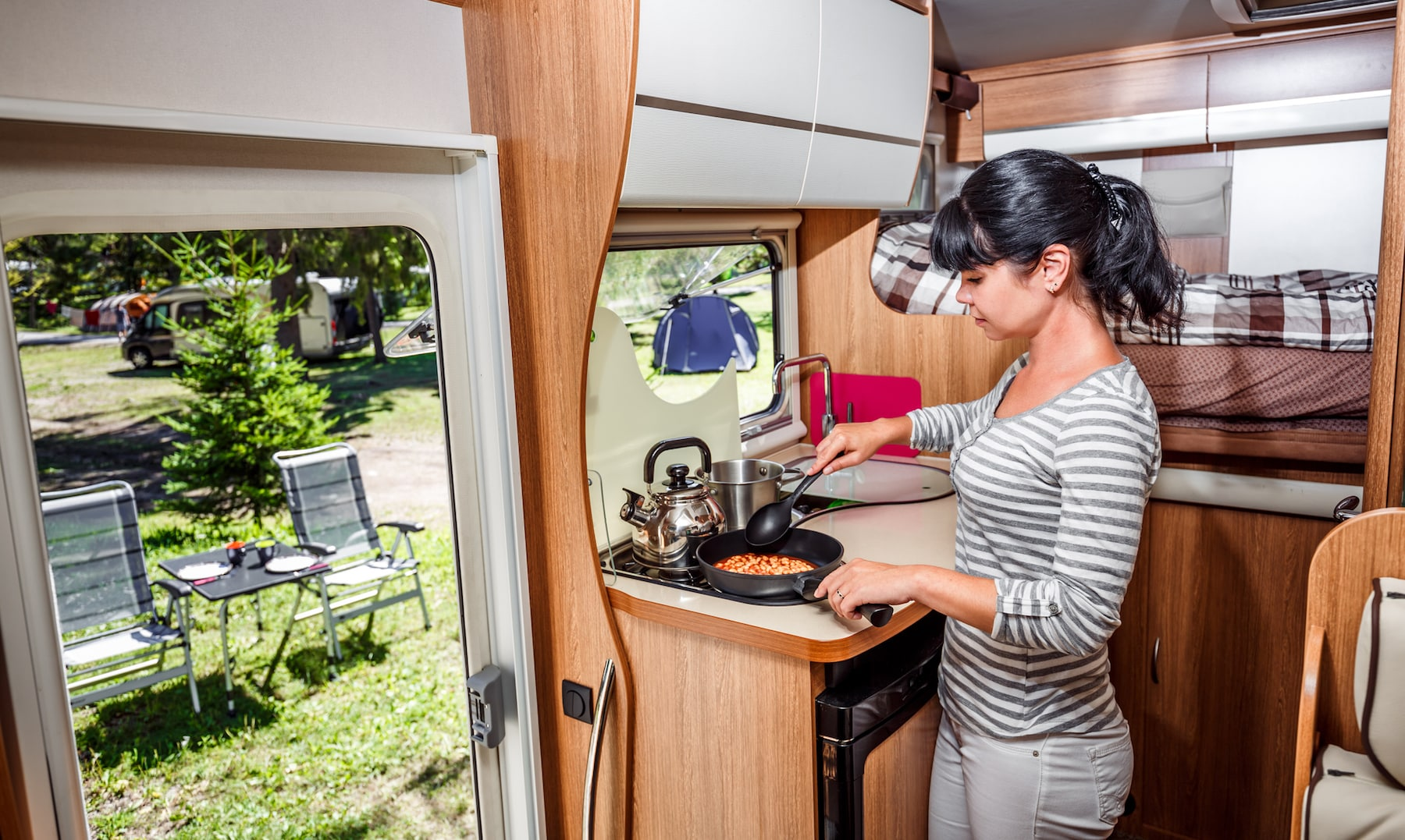 Woman cooking in camper, motorhome interior. Family vacation travel, holiday trip in motorhome, Caravan car Vacation. (Woman cooking in camper, motorhome interior. Family vacation travel, holiday trip in motorhome, Caravan car Vacation., ASCII, 118 co
