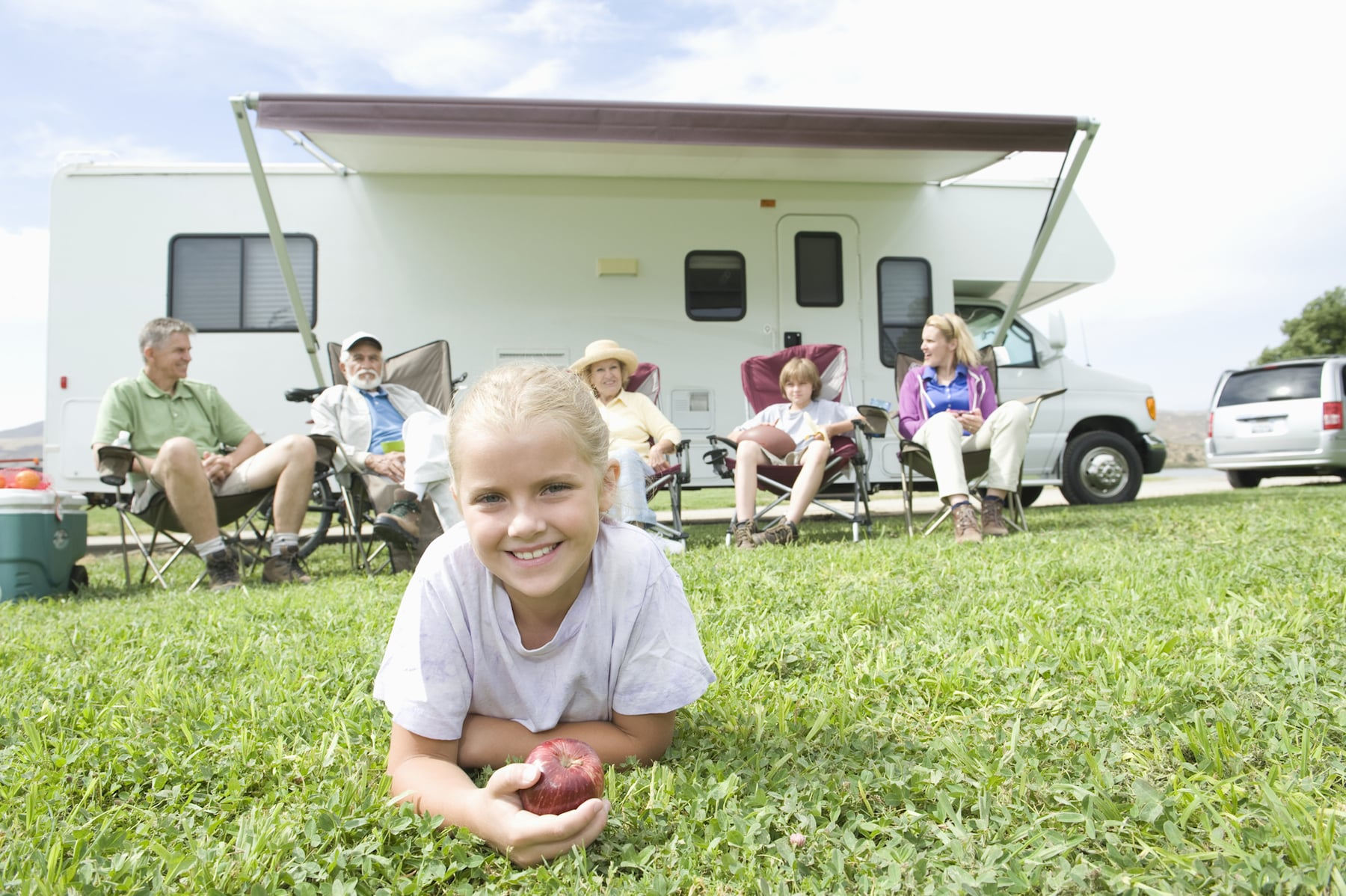 Portrait of a cute little girl lying on grass with family sitting outside RV home