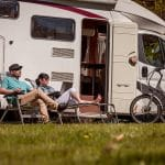 Woman with a man resting near motorhomes in nature. Family vacation travel, holiday trip in motorhome RV, Caravan car Vacation. (Woman with a man resting in camp chairs near motorhomes in nature. Family vacation travel, holiday trip in motorhome RV,