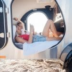 Reading messages. Appealing woman lying in trailer near her boyfriend using smartphone reading messages