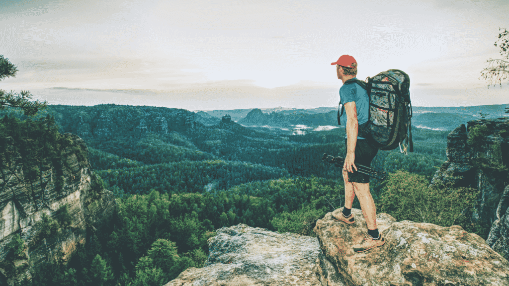 A man standing on a rock looking out at a spectacular view while hiking.