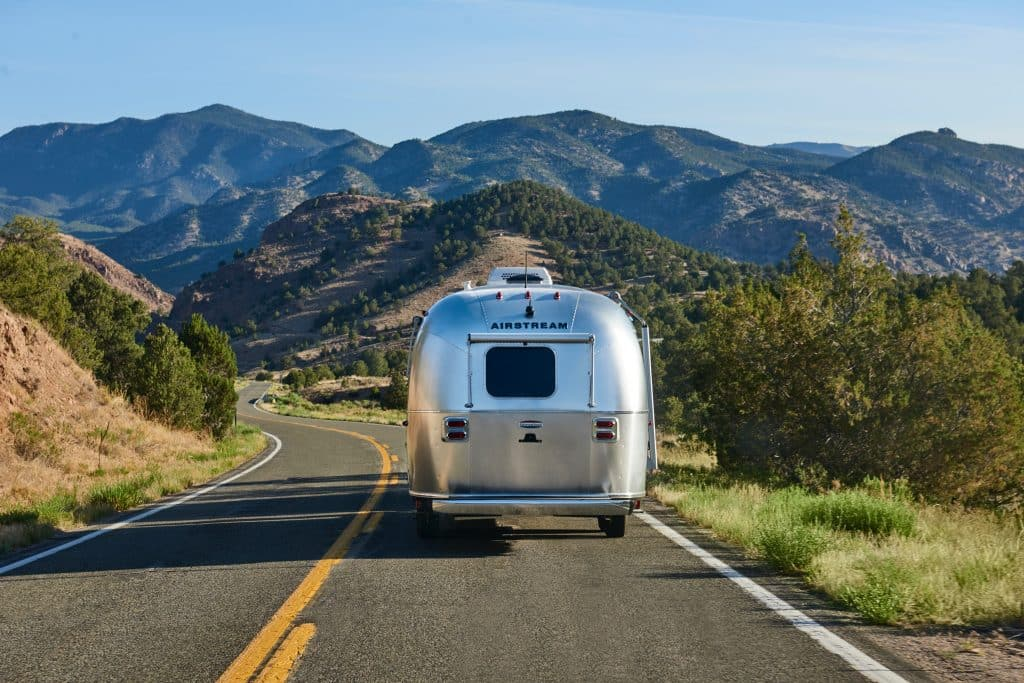 A towable Airstream RV winds through the mountains.