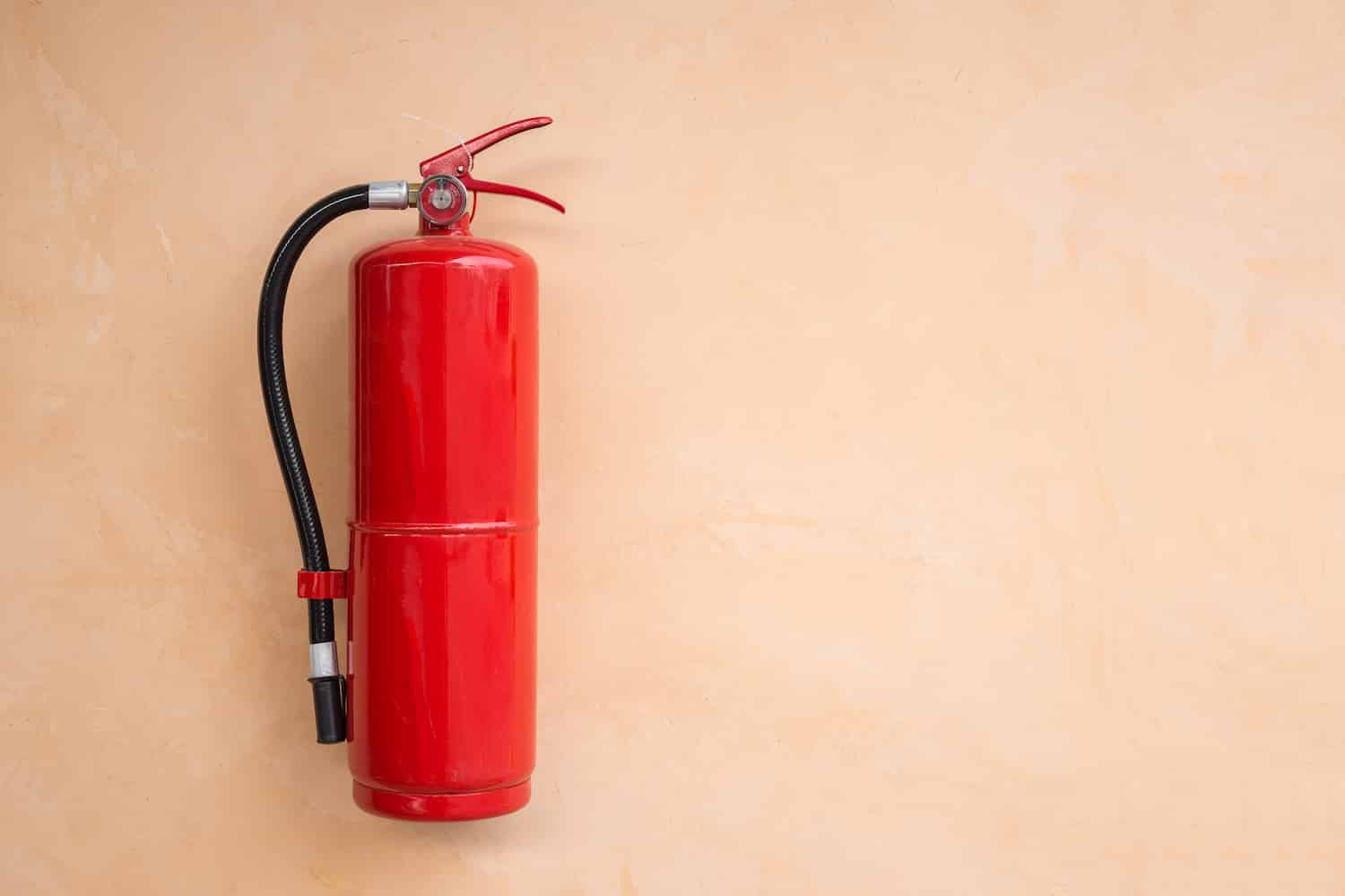 New red fire extinguisher tank on orange wall