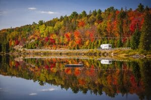 Fall forest with colorful autumn leaves and highway 60 reflecting in Lake of Two Rivers. Algonquin Park, Ontario, Canada. (Fall forest with colorful autumn leaves and highway 60 reflecting in Lake of Two Rivers. Algonquin Park, Ontario, Canada., ASC