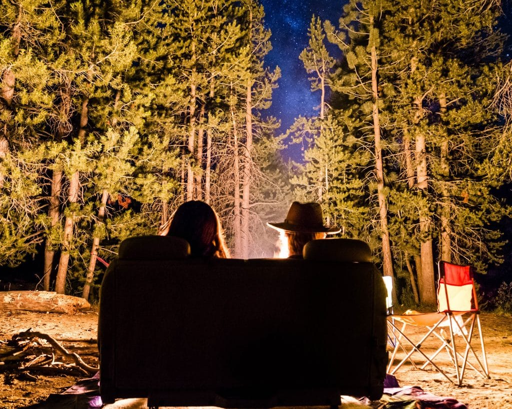 A couple sitting in from of a campfire at the perfect camp site
