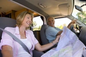 retired woman reading map in motor home with husband driving