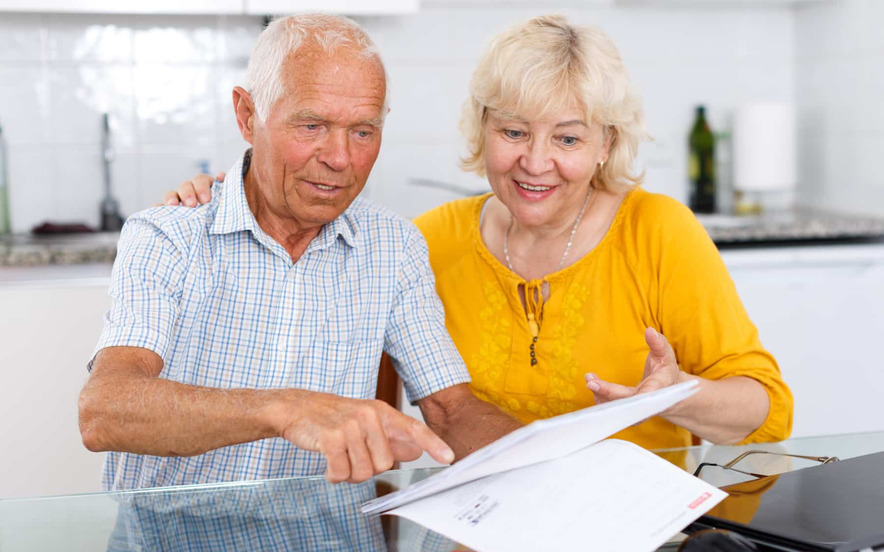 Portrait of a mature family couple with documents at kitchen table