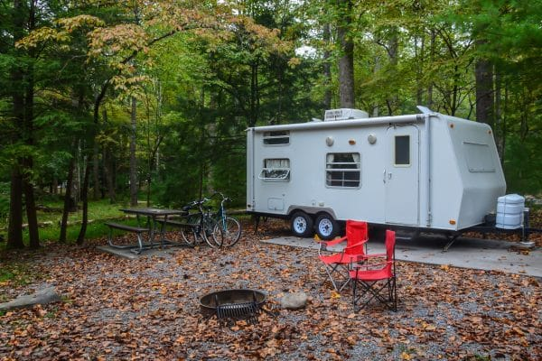 Camp trailer set up in campground site with bicycles