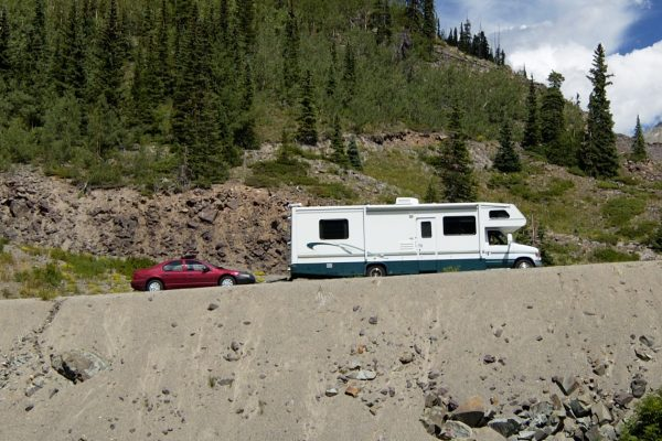 A Class C motorhome towing a car, a toad