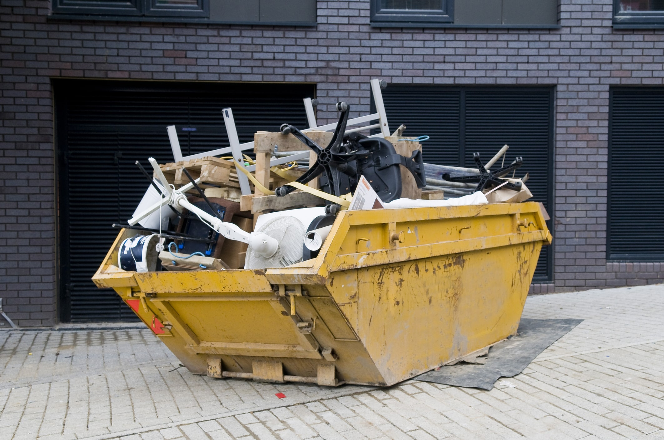 Yellow industrial skip full of disused office equipment