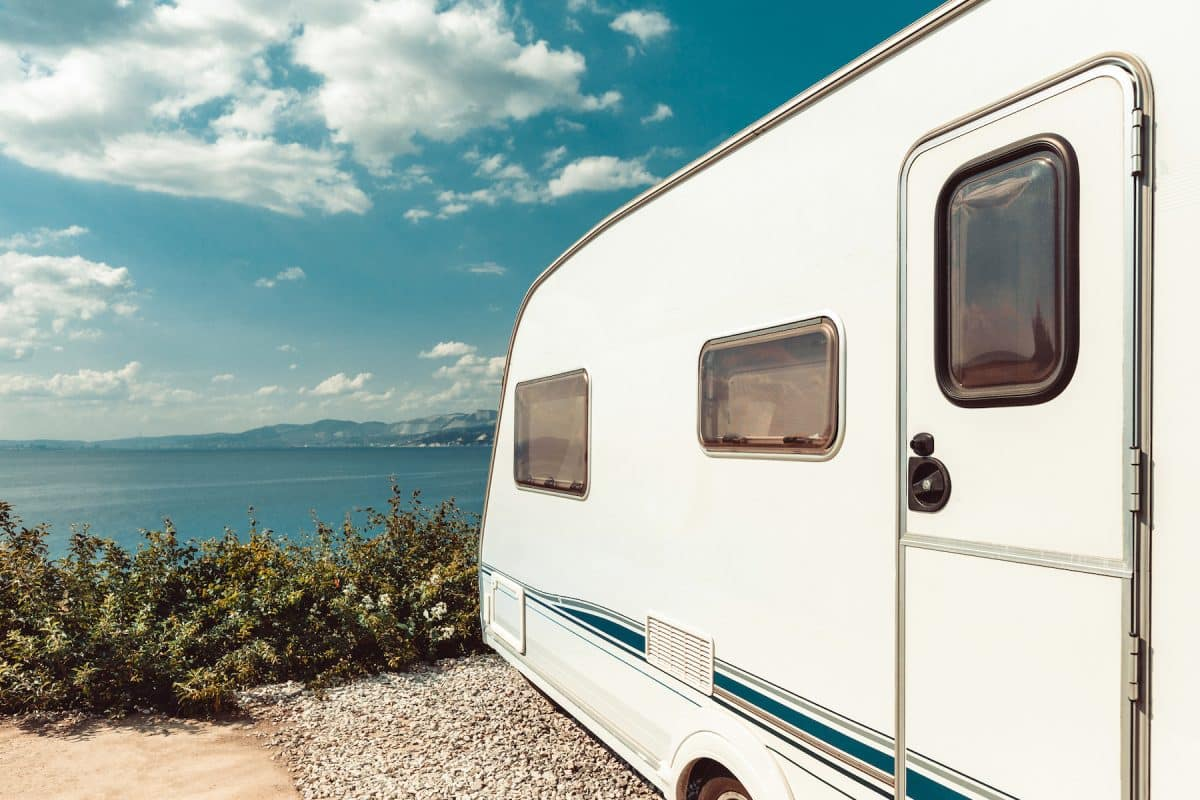 RV Trailer Near Sea, Beach And Blue Sky. Summer Holidays Road Trip Travel Concept