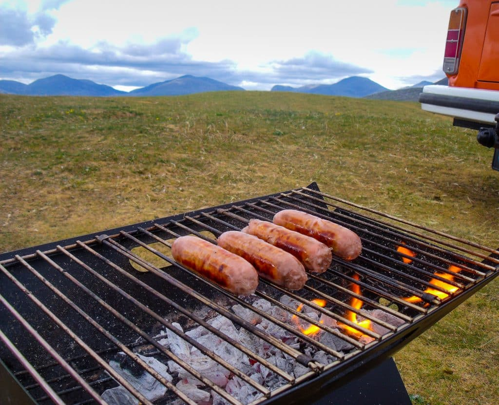 Four delicious sausages cooked to perfection on the traditional charcoal barbecue fiery grill. This scene on a camping road trip to the mountains. A typical Summer image when camping, travelling or having parties with family and friends.
