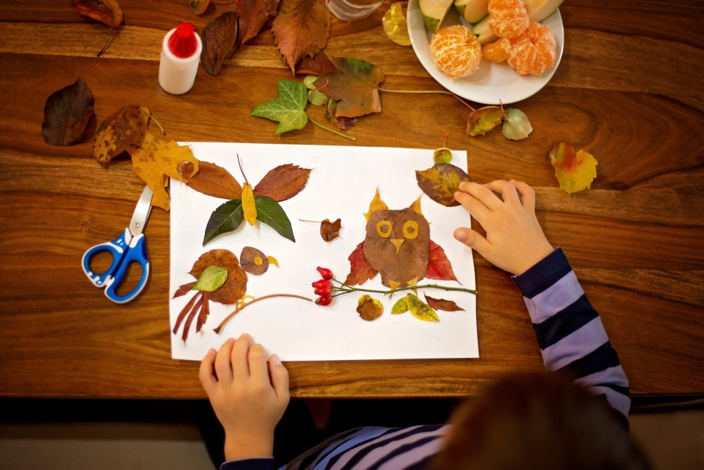 child, boy, applying leaves using glue while doing fall crafts arts