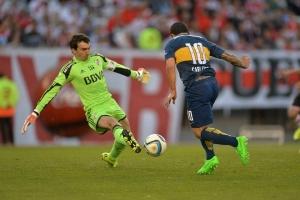 El jugador de Boca Juniors, Carlos Tévez (d), intenta driblar al guardameta riverplatense Marcelo Barovero (i). Agencia EFE.