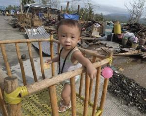 Un niño descansa entre los escombros de las casas dañadas por el paso del tifón Nock-Ten por la localidad de Polangui, provincia de Albay (Filipinas). EFE
