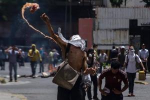 Manifestante lanza un objeto incendiario a integrantes de la Policía Nacional Bolivariana. EFE