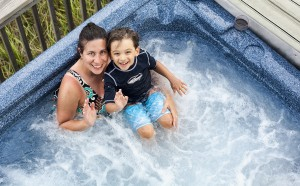 Woman and child in jacuzzi waving to camera