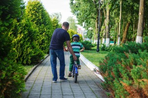 Father help son to ride bicycle in summer park. Back view