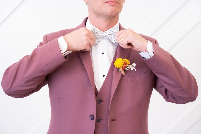 Groom Tying White Bow Tie with Light Maroon Suit for Groom's Attire for a Citrus Wedding