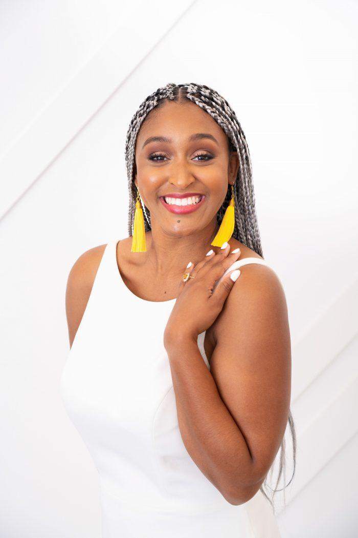 Bride Wearing Yellow Tassel Earrings Against Minimalist White Wedding Dress by Maggie Sottero