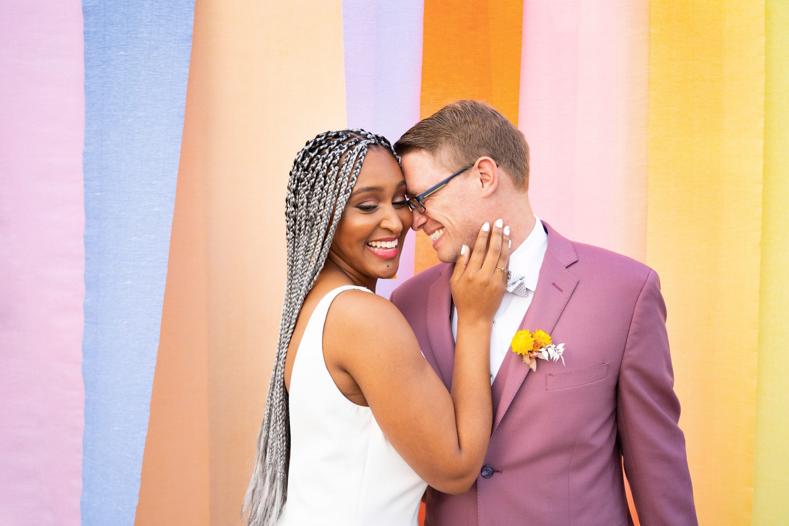 Interracial Couple Kissing in Front of Color Block Background at Citrus Wedding