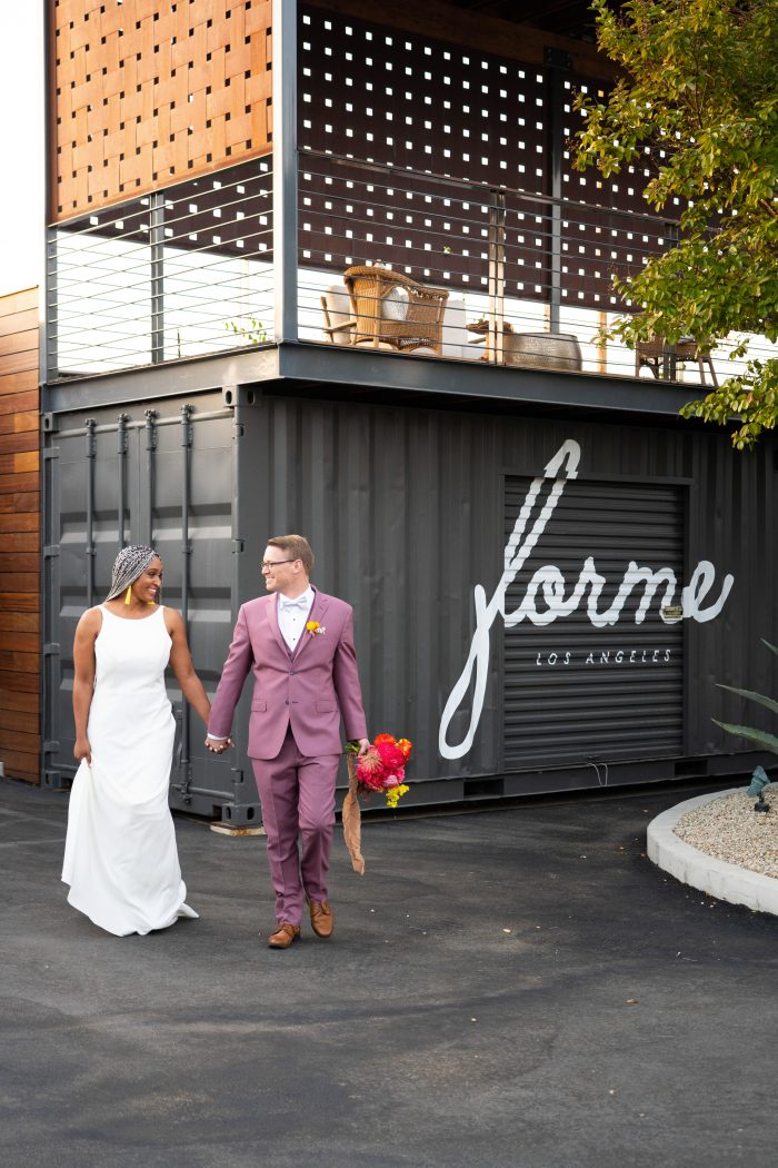Groom Outdoors Walking with Bride Wearing Minimalist Wedding Dress Called Claudia Dawn by Maggie Sottero