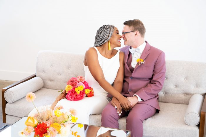 Groom on Couch with Real Bride Wearing Minimalist Wedding Dress at Reception