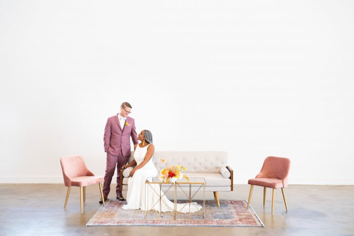 Bride and Groom on Couch with Bride Wearing Minimalist Wedding Dress at Reception
