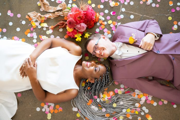 Bride and Groom Laying on the Ground Surrounded by Colorful Confetti at Citrus Wedding