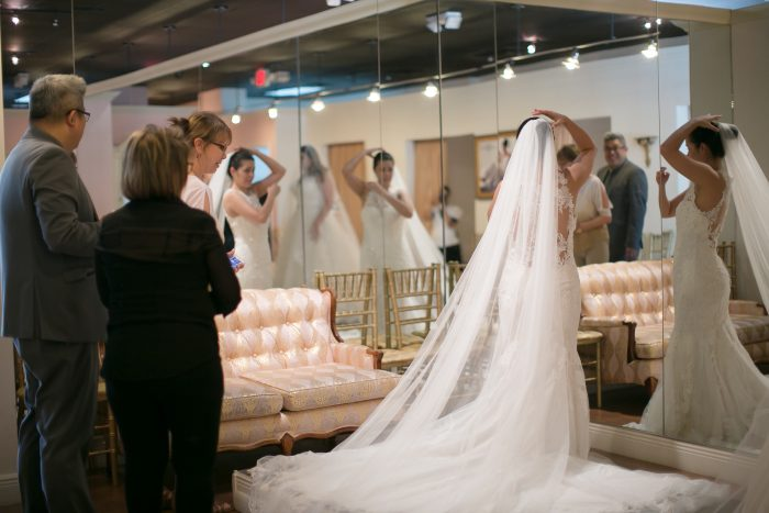 Bride Trying on Veil with Wedding Dress by Maggie Sottero