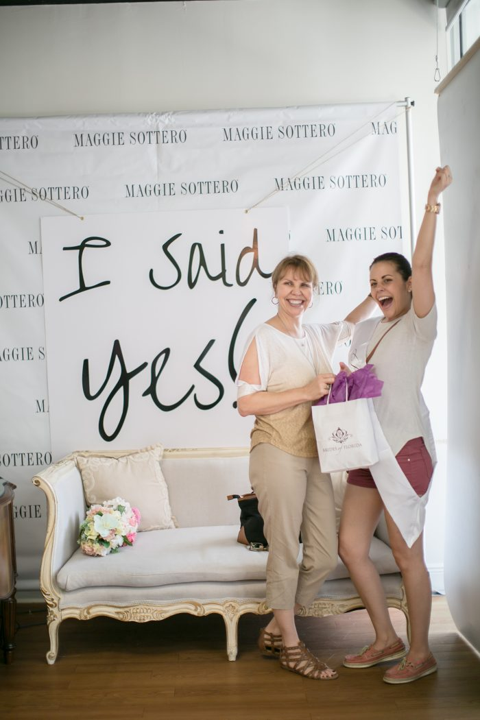 "Bride with ""I Said Yes"" sign in a bridal boutique"