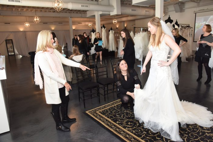 Bridal Consultants Assisting Bride in Wedding Dress Fitting