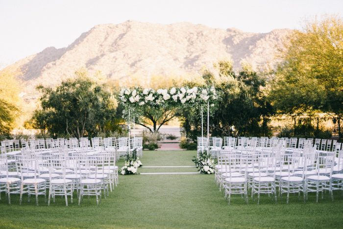 Clean Wedding with Archway Featuring Green and White Florals