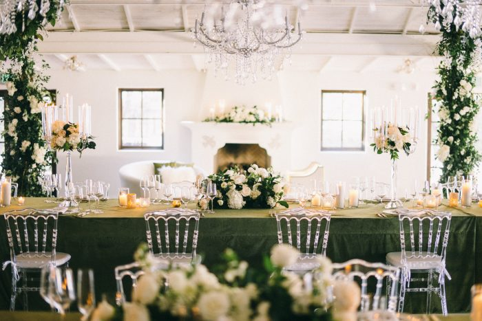 Archway in Modern Wedding Venue Featuring Green Florals and a Fireplace in the Centure