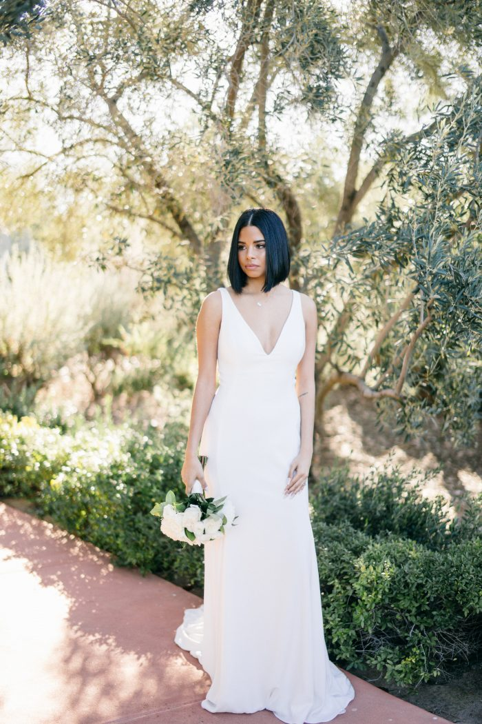 Black Bride Wearing V-neck Crepe Wedding Dress Called Fernanda by Maggie Sottero While Holding a White Bouquet
