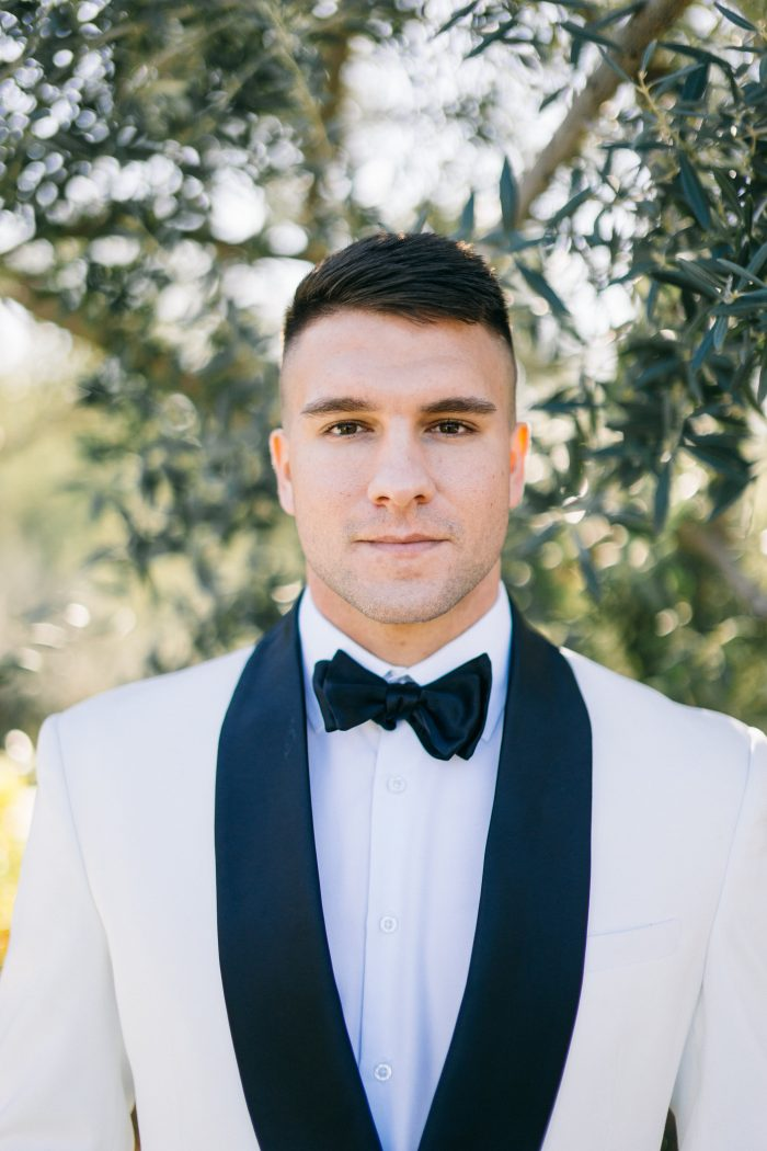 Groom Wearing Black Bow Tie with Modern White Suit Coat
