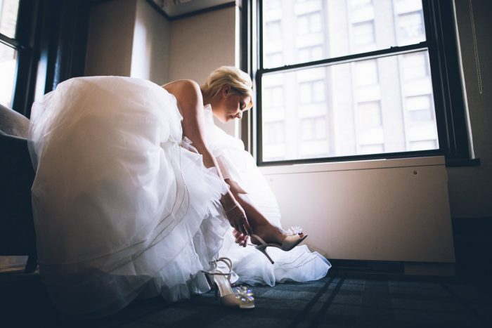 Bride Putting on White Wedding Shoes