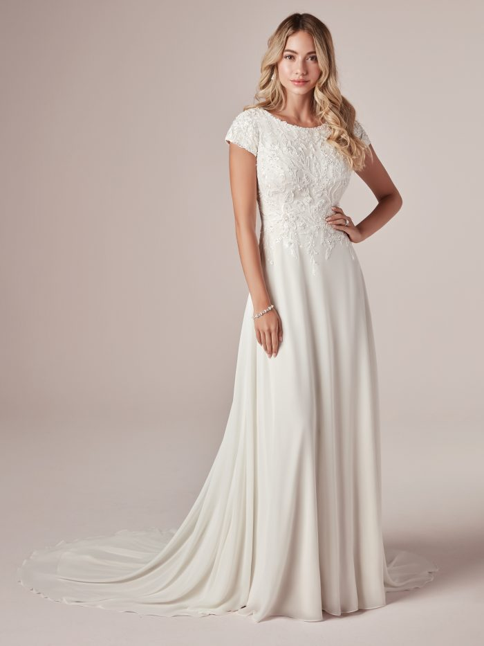 Model Wearing Cap-Sleeve Modest Sheath Wedding Dress Called Mercy Leigh by Rebecca Ingram