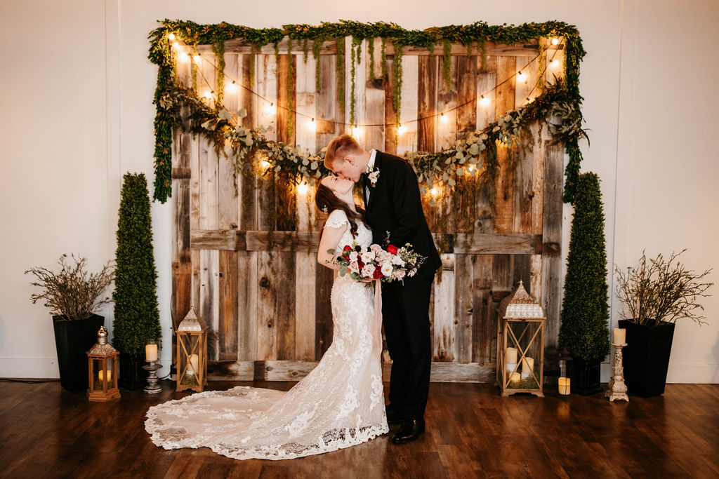Groom Kissing Bride Wearing Modest Lace Wedding Dress by Maggie Sottero at Rustic Winter Wedding